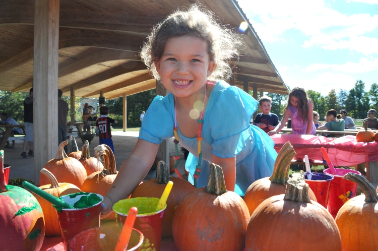 4 year-old Naomi Lipson of New Paltz paints a pumpkin at last Saturday's New Paltz Central School District's Foundation for Student Enhancement kids event at the Field of Dreams.